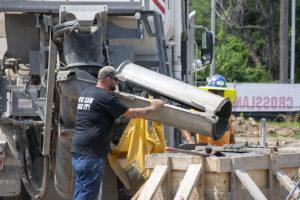 A concrete operator lines a volumetric mixer chute up over a wooden pedestal form at the Tulsa Expo Center in Tulsa, OK.