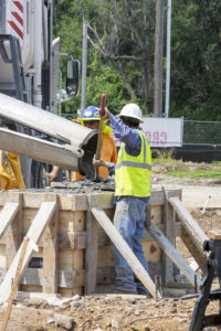 A concrete finisher moves volumetric concrete from the chute to a corner of a wooden form.